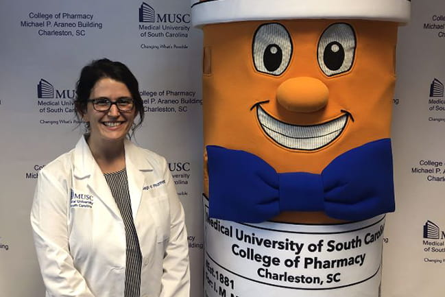 Kristen Bordner, Class of 2024, poses with new pharmacy mascot Phil the Pill.